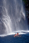 Couple swimming under waterfall, Falls of Balleine, St. Vincent, Caribbean