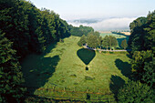 Shadow of a balloon on woodland, Valley of Weser, Lower Saxony, Germany