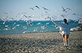 Girl running along the beach chasing seagulls, Lake Michigan, USA