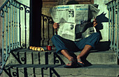 French breakfast, man reading newspaper on the stairs