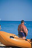 Schlauchboot vor einem korpulenten Mann am Strand, Mallorca, Balearen, Mediterrane Länder, Spanien