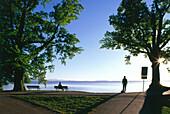 Two people at lake Chiemsee, Chieming, Upper Bavaria, Germany