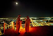 Sheiks standing on a roof deck at night, Bur Deira, Dubai, United Arab Emirates