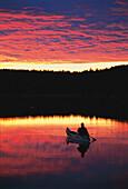 Canoe on lake at sunset, Vaestergoetland, Schweden