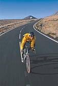 Man on a racing bike riding along a country road, Fuerteventura, Canary Islands, Spain