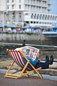 Man sitting in a deckchair while reading a newspaper, Llandudno, Gwynedd, Wales, United Kingdom