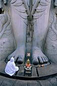 A person cowering in front of the feet of the giant Sri Gometeswara Statue, Sravanabelagola, Karnataka, India