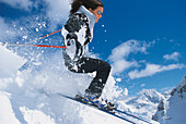 Freeriding, eine Frau fährt Ski vor blauem Himmel