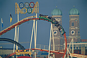 Roller coaster in front of Church of Our Lady, Oktoberfest Munich, Bavaria, Germany