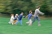 Mann and four kids running through meadow, Bavaria