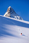 Young man skiing in deep powder snow in front of Matterhorn, Grisons, Switzerland