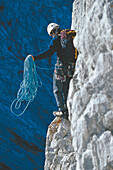 Climber with rope on rock face