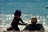 Kind graebt Mutter ein, Strandurlaub