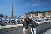 Couple admiring the view across Nice harbour, Nice, Cote D'Azur, France