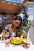 Woman enjoying a meal and a cocktail at a restaurant, Playa del Ingles, Gran Canaria, Canary Islands, Spain