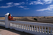 Young woman sitting on railing overlooking Maspalomas, Gran Canaria, Spain