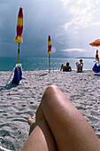 People lying on beach, Sardinia, Italy
