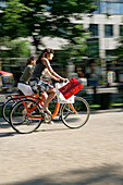 Two young women cycling along a road, Unter den Linden near Friedrichstrasse, Berlin, Germany