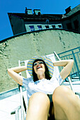 Laughing young woman sitting in a deck chair