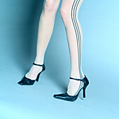 Young woman in stockings with stripes wearing high heel pump