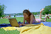 Young woman with laptop lying on towels at Starnberger See, Bavaria