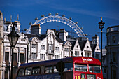 Street of London with a red bus and London Eye hovering above houses, London, England, Great Britain