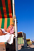 St. Peter Ording beach, Young woman relaxing in beach chair, St. Peter Ording beach, Schleswig-Holstein Germany