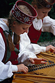 Two young women in traditional Danish clothes playing folk music, Jutland, Denmark