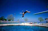 Boy jumping into swimming pool, Lake Constance, Arbon, Switzerland, Europe