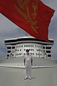 Queen Mary 2, Captain R.W.Warwick, Cunard flag, Queen Mary 2, QM2 Kapitaen und Commodore R.W.Warwick am Bug des Schiffes, im Vordergrund die Flagge der Reederei Cunard.