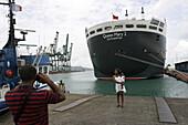 Queen Mary 2, Quay of Fort-de-France, Martinique, Queen Mary 2, QM2 Anleger fuer Kreuzfahrtschiffe im Hafen von Fort de France, Martinique. Eine einheimische Familie macht ein Erinnerungsfoto.