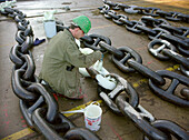 Worker painting the anchor chain white, dry dock, Queen Mary 2, Saint-Nazaire, France
