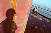 Worker and shadow, dry dock, Queen Mary 2, Saint-Nazaire, France