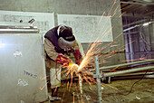 Worker weldong steel construction, dry dock, Queen Mary 2, Saint-Nazaire, France