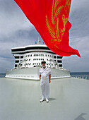 Commodore Ronald Warwick standing on the deck under a red flag, Cruise ship Queen Mary 2