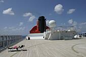 Queen Mary 2, Sunbathing on the sundeck, Queen Mary 2, QM2 Ein Passagier sonnt sich auf dem Sundeck Hubschrauberlandedeck, Buch S. 160