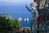 Weathered stone figure and group of tourists at the coast, Monte Solaro, Faraglioni, Capri, Italy, Europe