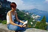 Young woman reading a book on a wall, Conca dei Marini, Amalfi, Campania, Italy, Europe