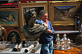 Mature man leaning at antique bust at the flea market, Porta Portese, Rome, Italy, Europe
