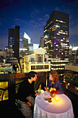 A couple at a roof terrace in the evening, PenTop Bar, Peninsula Hotel, New York, USA, America