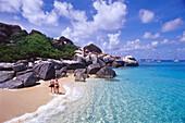 Couple strolling along a beach with rocks, The Baths, Virgin Gorda, British Virgin Islands, Caribbean, America