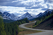 Alaska Highway in front of snow covered mountains, Yukon Territory, Canada, America