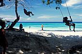 Children on a swing in the shadow on a beach, Winnifred Bay, Port Antonio, Portland, Jamaica, Caribbean, America