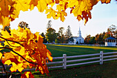 Church and autumnal trees in the light of the evening sun, Craftsbury, Vermont, USA, America