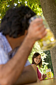 Two young people smiling at each other in beer garden, Munich, Bavaria