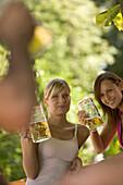 Two cheerful girls with beer steins in beer garden, Munich, Bavaria