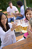 Three young women, friends, having fun in a beer garden, lake Starnberg See, Bavaria, Germany