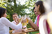 Four young people toasting each other in beer garden, Munich, Bavaria