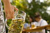 Female hand holding beer stein in beer garden, Munich, Bavaria