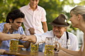 Cheerful people playing game in beer garden, Fingerhakeln, Munich, Bavaria